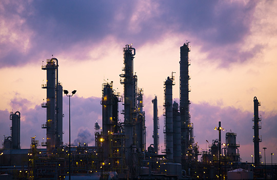 Refinery stacks with a purple cloudy sky